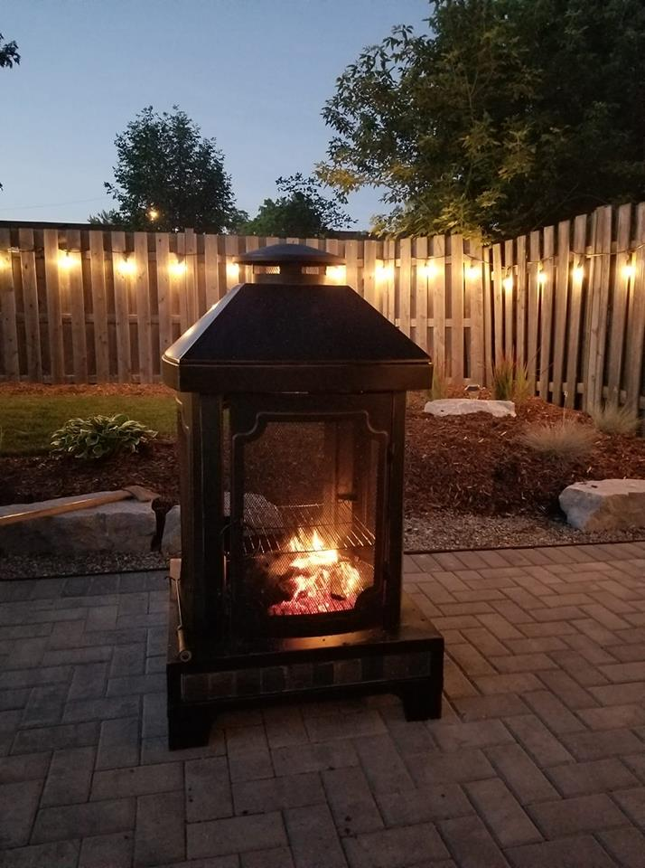 Metal fire pit with a small fire inside on an outdoor patio