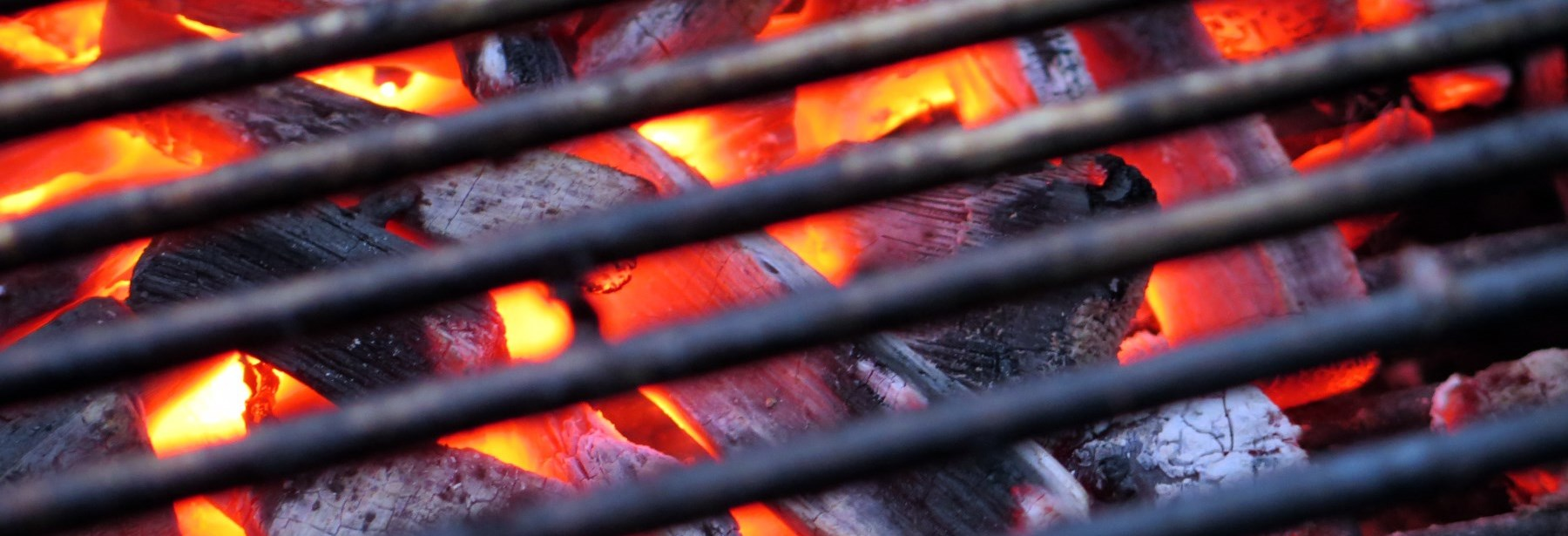 Barbeque grill showing coals and fire below