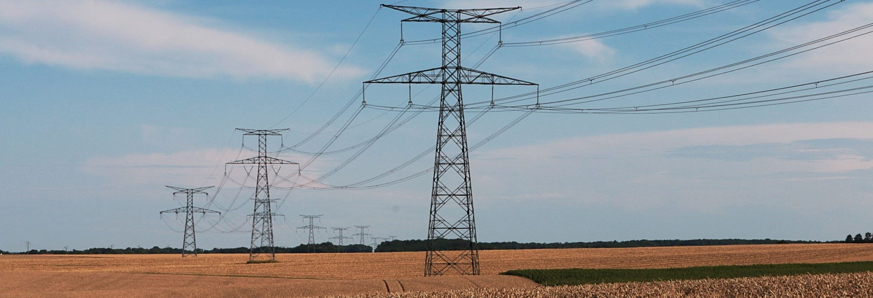 hydro towers in a field against a blue sky